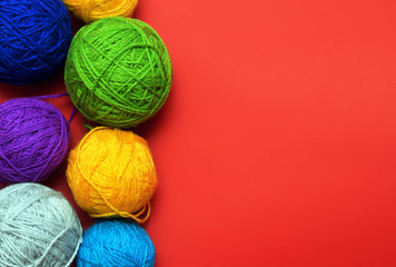 Multicolored tangle of yarn on  red background