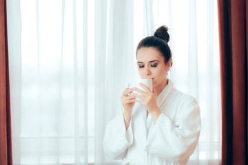 Woman in Bathrobe Starting Morning with a Cup of Coffee