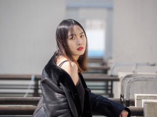 Portrait of sexy brunette woman in black jacket with blur buildings background. Outdoor fashion portrait of glamour young Chinese cool stylish lady. Emotions, people, beauty and lifestyle concept.