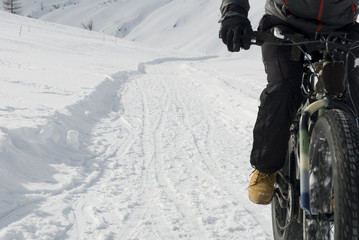 man use electric bicycle, e-bike, ebike, pedal on snow covered road, downhill mountain, specific bike with wide wheels to go on snow, called fat bike, winter, alps, Simplon Pass, Swiss