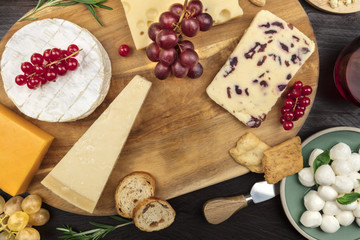 Various types of cheese on a dark rustic background with copy space
