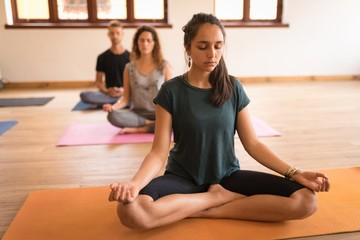 Young people meditating in the gym