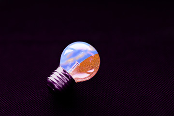 electric lamp inside with the sky and the sand on a dark background