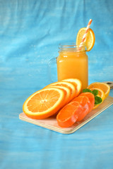 Slices of orange, mandarin and lemon and yellow juice in a glass jar on blue background