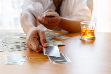 Close up of businessman's hands holding playing cards with money and whiskey glass on the table, Gambling concept
