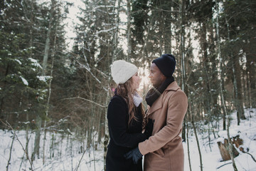 Multiracial couple bonding in winter forest