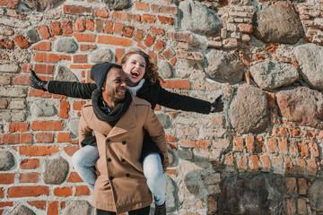 Couple having fun at brick wall
