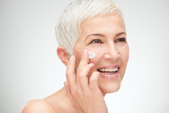 Head shot of beautiful senior woman putting on the cream.