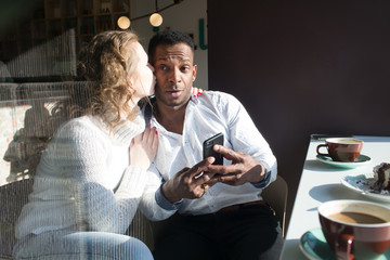 Couple using smartphone in cafe