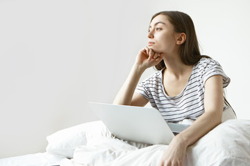 Attractive young female blogger with dark hair working on content for her online blog using laptop, having thoughtful dreamy look, sitting at white wall with copy space for your promotional content