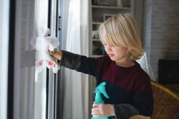 Boy cleaning window with rag cloth