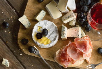 Platter with Spanish ham jamon serrano or Italian prosciutto crudo sliced Italian hard cheese pecorino toscano homemade dried meat salami glasses of red wine and pistachios on old wooden board