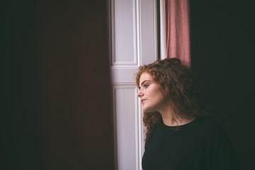 Thoughtful woman leaning on door