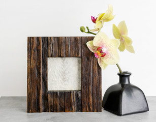 Wooden photoframe mockup with yellow orchid against white wall. Interior design concept. Text space