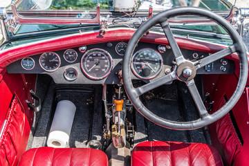 Cockpit eines englischen Oldtimers aus den 1930ern mit roten Ledersitzen und einer Küchenrolle