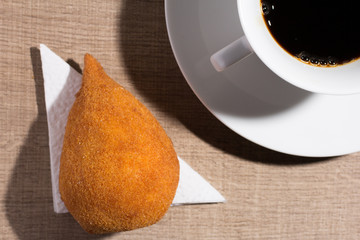 Coxinha is a deep fried food, traditional in Brazil. Snack and cup of coffee on wood, overhead.