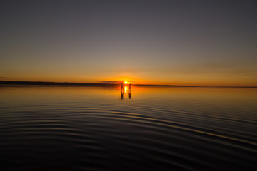 Young couple is walking away in the water on summer beach. Sunset over the sea.Two silhouettes against the sun. Just married couple in romantic love story. Man and woman in holiday honeymoon trip.