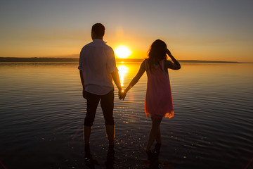 Young couple is walking in the water on summer beach. Sunset over the sea.Two silhouettes against the sun. Just married couple hugging. Romantic love story. Man and woman in holiday honeymoon trip.
