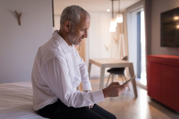 Businessman using a smart phone on bed