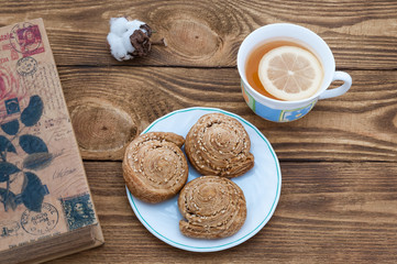 The book, tea and biscuits on the table of dark boards.