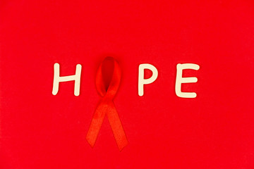 """Wooden letters """"Hope"""" with red tape as symbol of AIDS / HIV illness isolated on red background"""