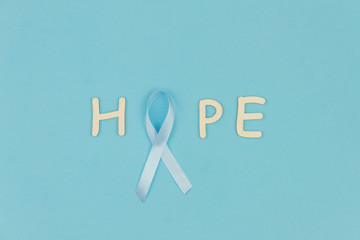 """Wooden letters """"Hope"""" with cyan / blue tape as symbol of men illness prostate cancer on cyan / blue background"""