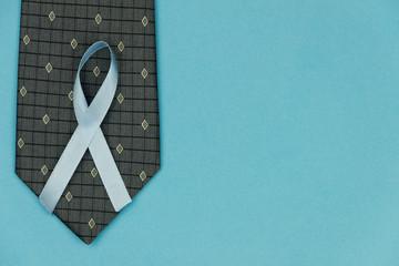 Cyan / Blue tape as symbol of men illness prostate cancer lying on black men tie on cyan / blue background