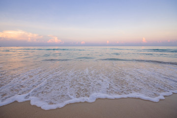 dawn view of the ocean beach shot on an ultra-wide angle lens landscape of pink clouds and blue water and yellow sand