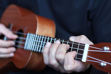 close up ukulele fretboard in musician hands