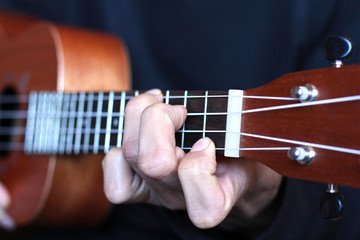 left musician hand clamps the chord on the ukulele fretboard