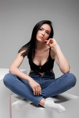 attractive sexy female in black brassiere and jeans sitting in lotus pose on cube in studio on gray background