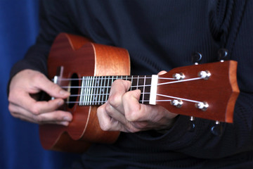 musician plays on ukulele, small depth of field