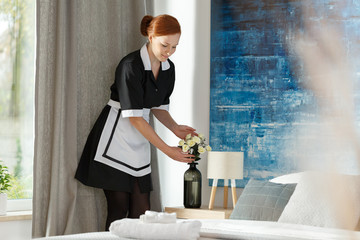 Maidservant putting flowers into vase