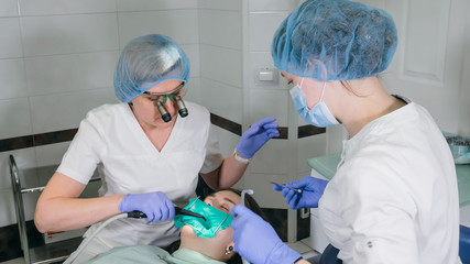 Woman at dentist clinic gets dental treatment to fill a cavity in a tooth. Dental restoration and composite material polymerization with UV light and laser. The doctor works with an assistant.