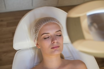 Woman getting beauty treatments while lying on salon bed