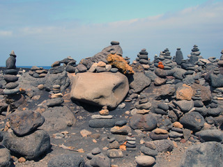 towers of stacked pebbles and stones in different colours in a large arrangement on a black sand beach with blue sky