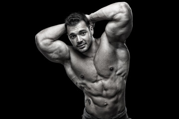 Handsome muscular male posing in front of black background