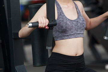 Woman exercising in fitness gym for good health. Athletic young woman exercising equipment at gym, workout in fitness center.
