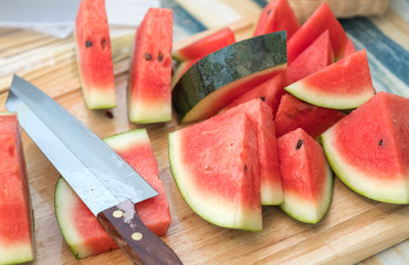 Watermelon sliced with knife on a wooden butcher.