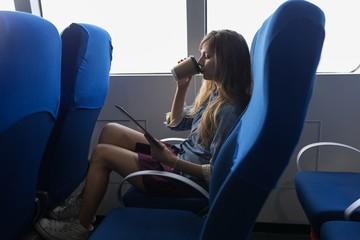 Beautiful woman using digital tablet while having coffee