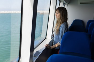 Woman looking through window while sailing in cruise ship