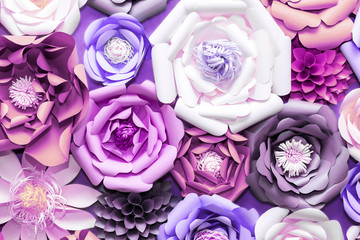 Colorful paper flowers on wall. Handmade artificial floral decoration.  Spring abstract beautiful background and texture. Ultraviolet tone, color of the year