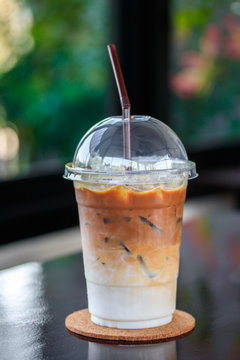 Iced caramel macchiato coffee in plastic glass with straws, take away cup on wooden table in cafe and blurred garden background, Selective focus.