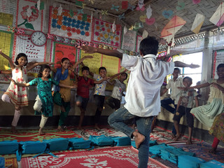 A Rohingya boy plays a game with classmates at a makeshift school in Kutupalong refugee camp in southern Bangladesh