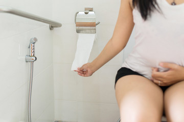 Woman holding toilet paper and using toilet in morning