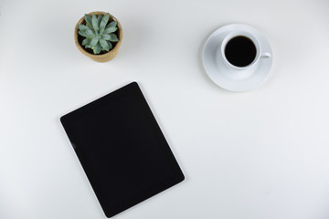 Blank digital notepad or tablet computer, spectacles, potted succulent and coffee on a white desk in an office in an overhead view with copy space