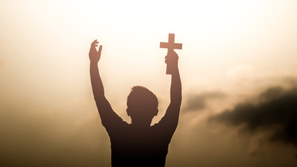 Human hand holding christian cross with light sunset background