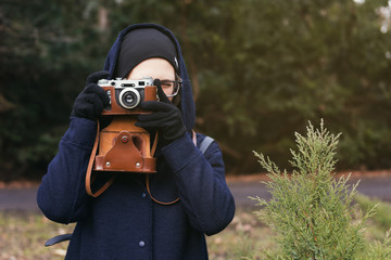 Young woman holding retro photo camera and taking photo in the park. Autumn nature on background. Travel concept.