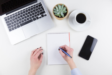 Businesswoman writing notes on a blank notepad in an overhead view of a neat white desk with laptop, mobile phone, coffee and her hands holding a ballpoint pen