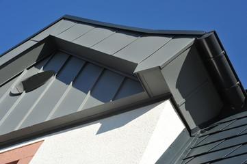 Schutzabschluss eines seitlichen Giebels aus beschichtetem Blech in Stehfalz-Verbund mit Dachrinne, und Rundfenster. Dach mit beschichteten Aluminiumschindeln gedeckt